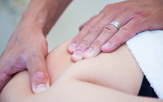An image showing a physiotherapist treat a female patient with deep tissue sports massage